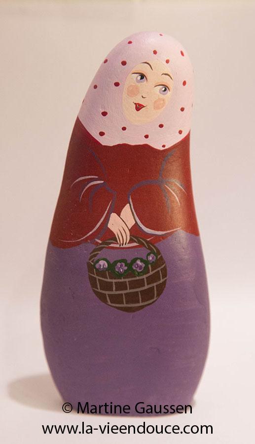 Le santon la marchande de violettes represente le village medieval de Tourrettes sur Loup